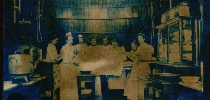 Photo of eight people mostly women, in a nineteenth century operating room.